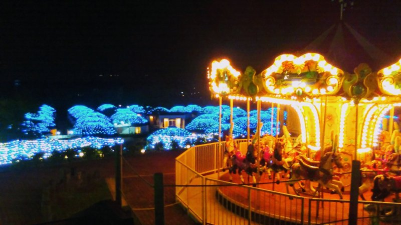Carousel and yurts lit up at night