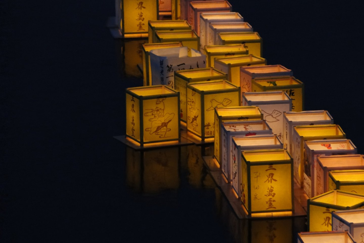 Lanterns float down the river in Sasebo to mark the end of Obon