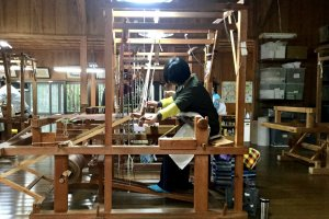 A weaver at the tall loom producing centuries-old traditional fabric