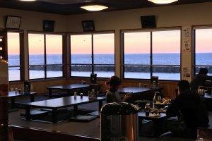 店内客席。夕陽に染まる海が美しい