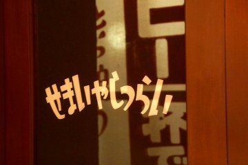 """Irashaimase"", welcome written right to left, on a Showa era shop window"