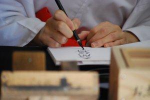 My goshuin getting stamped at Fukuoka's Dazaifu Tenmangu Shrine