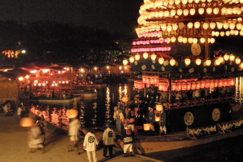 Makiwara boats with lanterns ablaze.