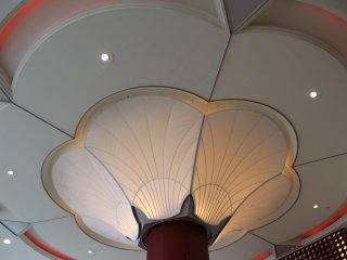 The load-bearing columns inside the hotel lobby lead to artfully designed lighting along the entrance ceiling
