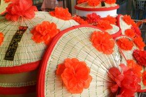 Những chiếc nón hanagasa đính hoa đỏ tươi sáng.