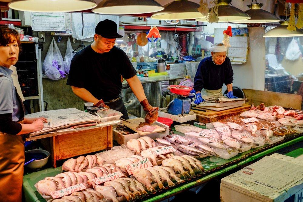 Les vendeurs préparent avec dextérité les fruits de mer frais pour les clients locaux