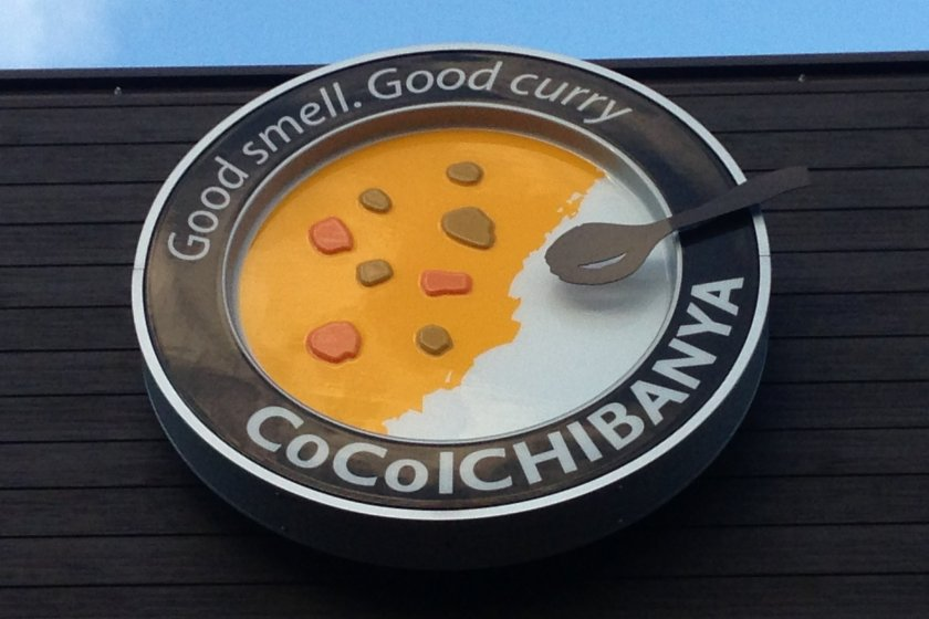 Coco ICHIBANYA'S sign accurately depicts its curry dishes; rice on one side with curry poured onto the other side of the plate