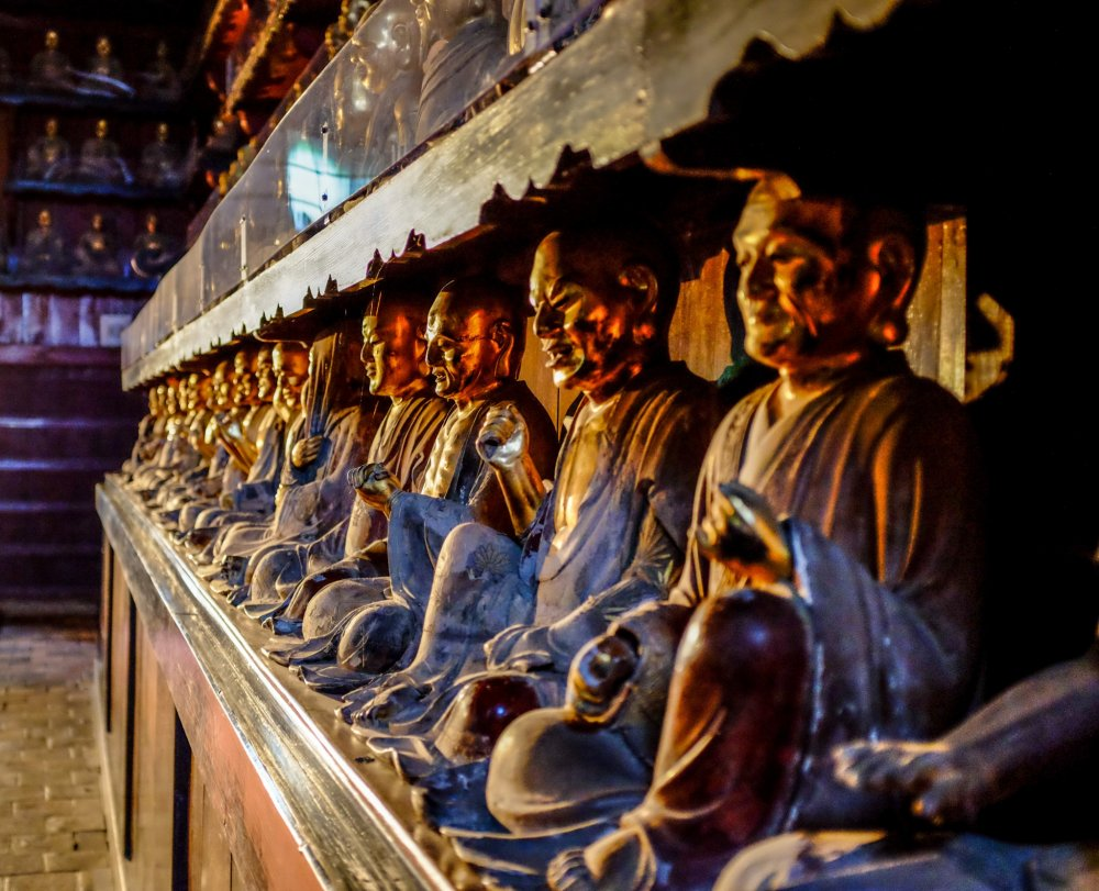 The Buddhist statues line the left and right side walls, each statue represented by a different face and gesture