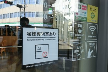 """Designated smoking room"" mark outside a coffee shop in Yokohama City."