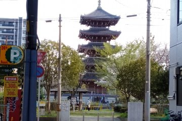 The pagoda of Kosho-ji Temple peeking through two modern buildings