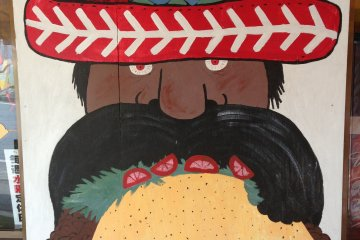 This sign invites passers by to come in to try the jumbo taco, which absolutely does NOT come with moustache hair in it