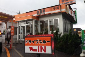 Yoshinoya's many restaurants are trimmed in orange and white with its name in kanji and English written in black