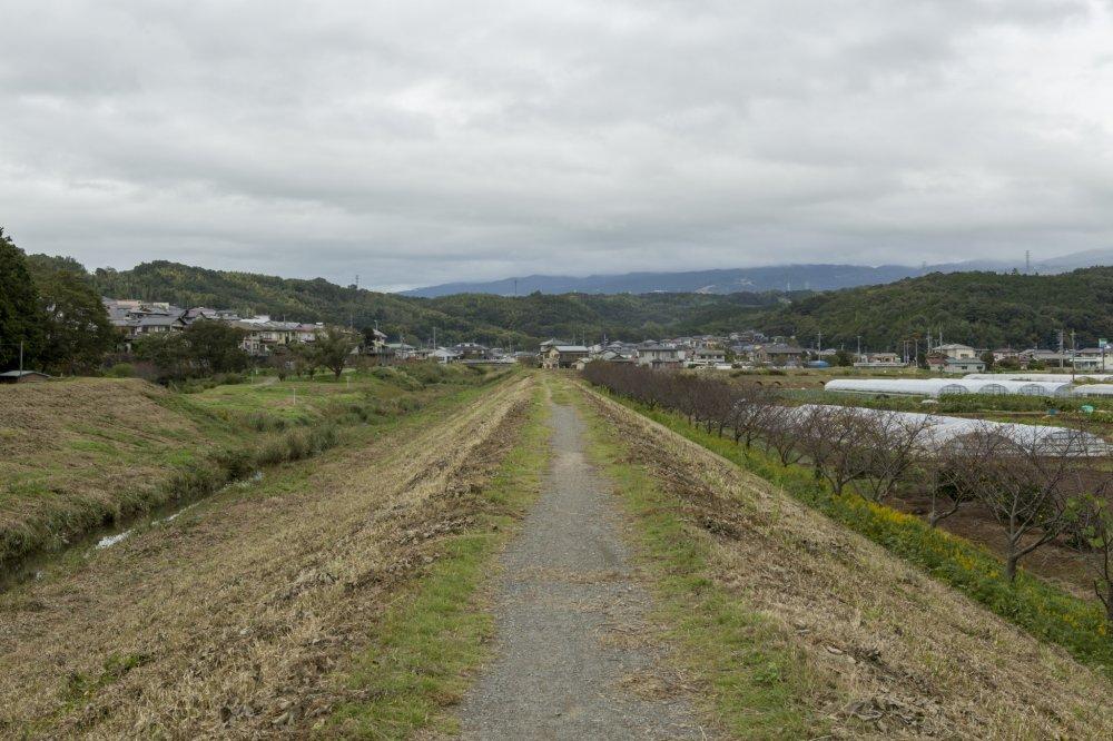 Sungai mengalir melewati kota dan pegunungan. Hulu sungai ini terletak di tempat tinggi yang menjadi latar belakang foto ini.