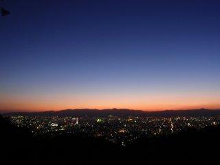Last rays of light slip behind the city