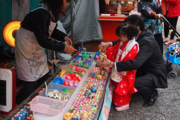 <p>Booths selling cotton candy, crepes and cartoon masks as well as game booths were set up outside the entrance.</p>