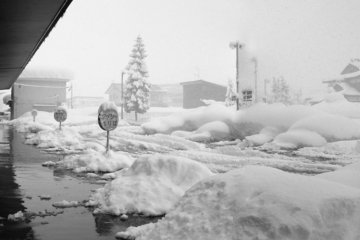 <p>Heavy snowfall at Urasa&nbsp;Station, my first experience with snow. Notice the sprinkler system on the left of the photograph (not very clear), which keeps the snow from piling up on sidewalks and roads&mdash;effective,&nbsp;but it can drench you comp