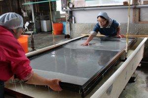 大きな木枠で紙漉きが行われている