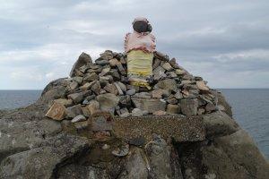 A small shrine on a cliff near the sea.