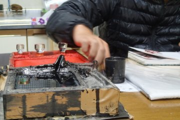 <p>Close up of ink well and stamp pad in background as Stamp #26 is being made</p>