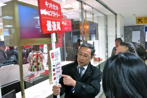 A KitKat Chocolatorystaff member holds a sign indicating the end of line and flavors available.