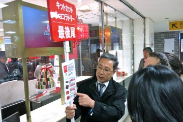 <p>A KitKat Chocolatory&nbsp;staff member holds a sign indicating the end of line and flavors available.</p>