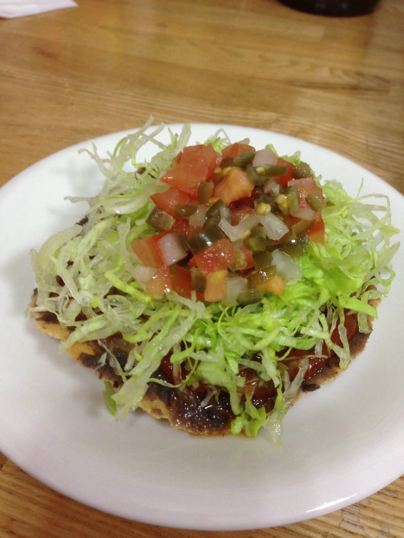 <p>tostada with homemade salsa and refried beans</p>