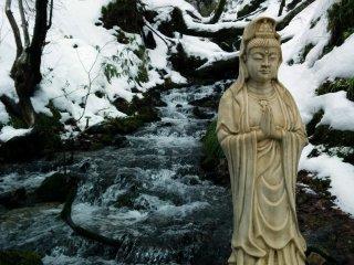 Một tượng Phật đứng lặng lẽ bên dòng suối đóng băng