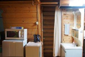 อีกมุมหนึ่งภายในบ้านพัก ทางซ้านเป็นตู้เย็น ไมโครเวฟ กระติกน้ำร้อน และสุดทางเดิน ซ้ายมือเป็นห้องอาบน้ำ และขวามือเป็นห้องสุขา