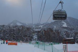 ภาพลิฟท์กำลังพานักสกีขึ้นไปบนยอดเขาข้างบน