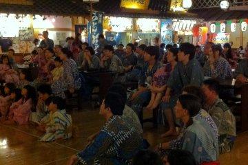 <p>ภาพครอบครัว คู่รักชาวญี่ปุ่นที่แต่งตัวด้วยชุดยูกาตะนั่งชมการแสดงในบรรยากาศย้อนยุค</p>